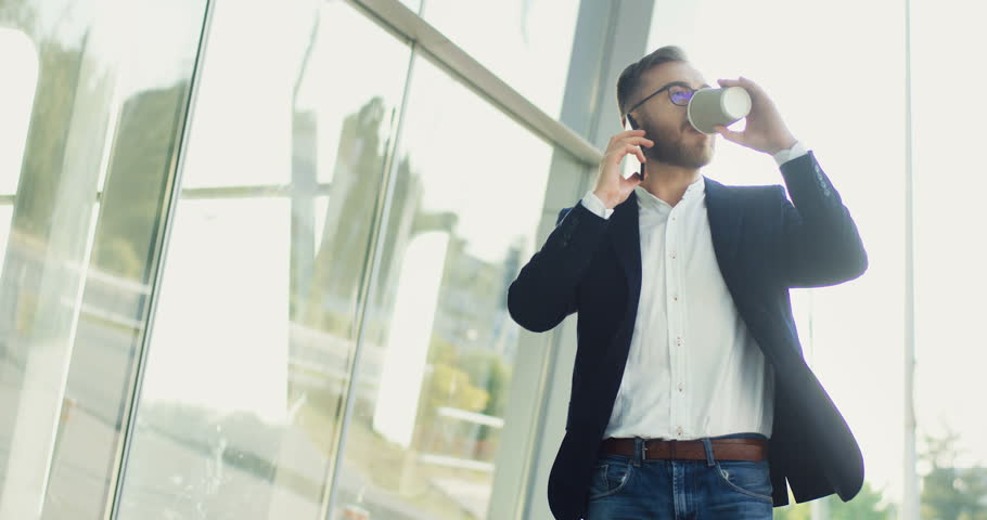 Caucasian young successful businessman walking to the office in the morning and speaking on the phone with a coffee in hands. | Shutterstock HD Video #1014757925