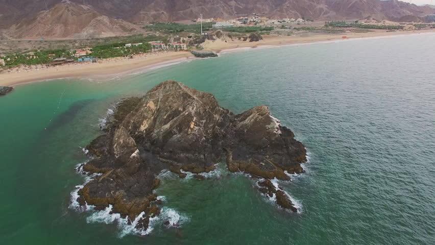 Flying over Rock Island in Sea Ocean Fujairah Aerial 4k video. View from Above resort in UAE | Shutterstock HD Video #1014785735