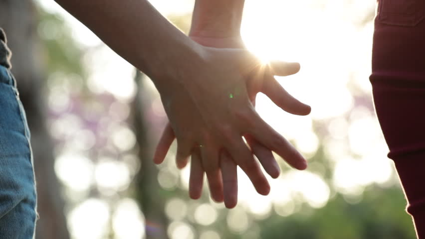 Close-up of hands joining together with sunlight flare in the background. Beautiful romantic moment between two lovers #1014812525