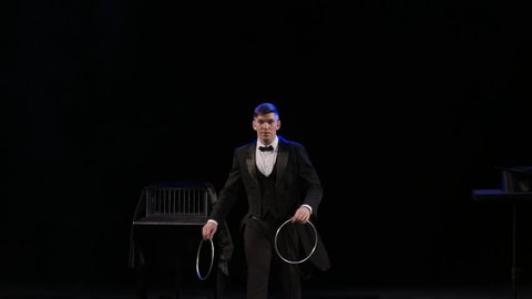 Magician manipulates iron hoops on thestage