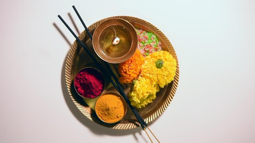 Hindu Pooja or Puja thali consisting of diya, flowers, kumkum, turmeric, rice grains arranged in a brass plate