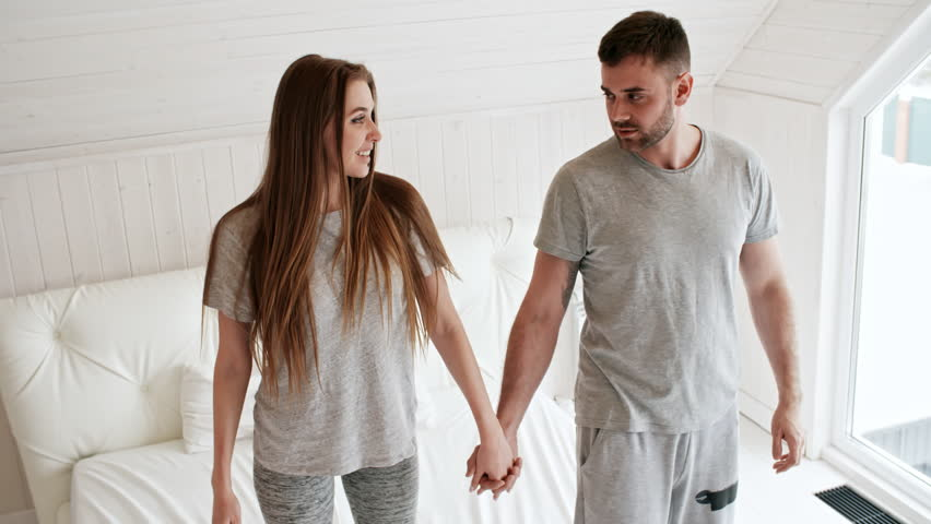 Handheld shot of happy young couple in sleepwear holding hands and standing on bed, then falling down on mattress and laughing
