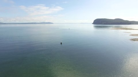 Aerial shot of two people fly fishing in Lake Taupo during the summer in New Zealand