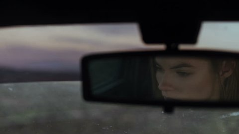 The girl's eyes in the car's rear view mirror, depression and despair