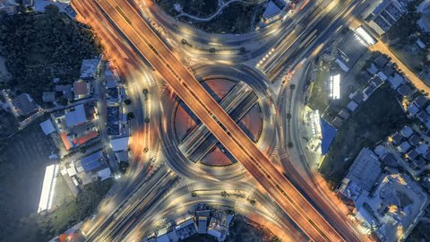 timelapse of night city traffic on 4-way stop street intersection circle roundabout in bangkok, thailand. 4K UHD horizontal aerial top view.