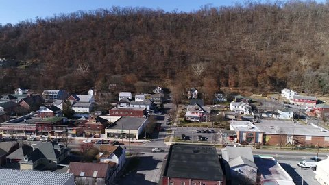 Aerial dollye to the left of a small town in Appalachia in the winter with a castle on the hill.
