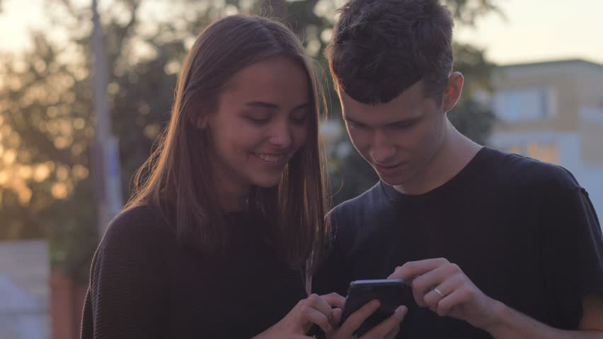 Couple sharing media in a smart phone in a park with buildings in the background | Shutterstock HD Video #1014930115