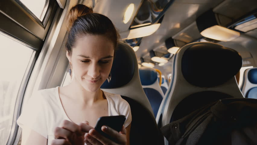 Close-up shot of beautiful happy European girl using smartphone social network app traveling on train window seat. | Shutterstock HD Video #1014930445