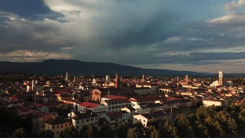 Aerial: Flight over a medieval Town of Lucca, Tuscany, Italy on a summer evening