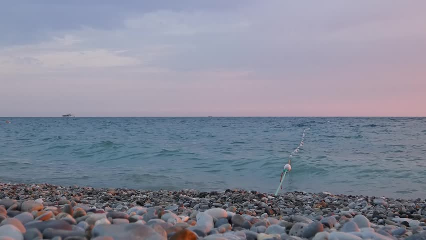 Summer evening at sea coast. Small waves surf on gray pebbles. Long rope with some floats goes into the water (seine or border).