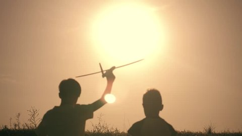 Two boys play with a wooden plane at sunset. Silhouette of children playing with airplane. Dreams of flying. The concept of children's games
