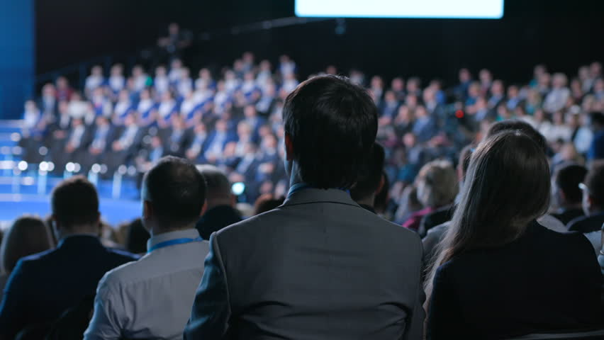 Confident official male team works at crowded forum for trading collaboration or education. Concept of briefing for economic partners or politicians indoors. Row of seats in large place for job worker | Shutterstock HD Video #1014974365