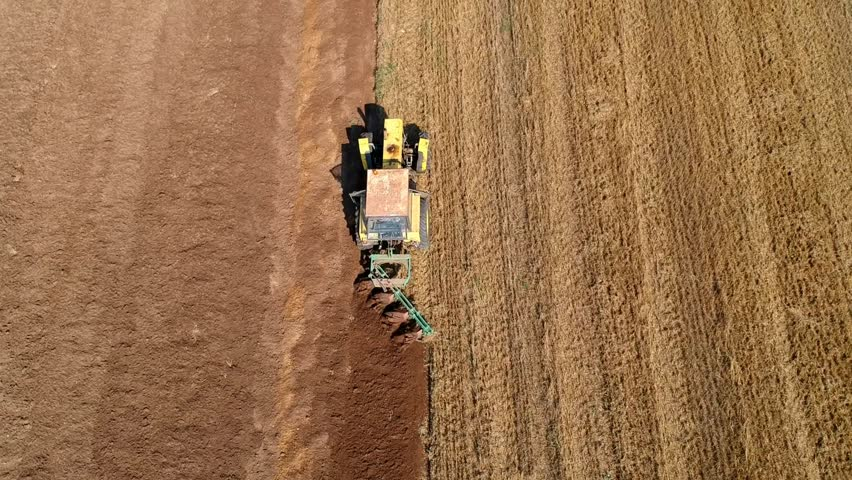 Aerial view on old tractor while plowing the soil after crops
