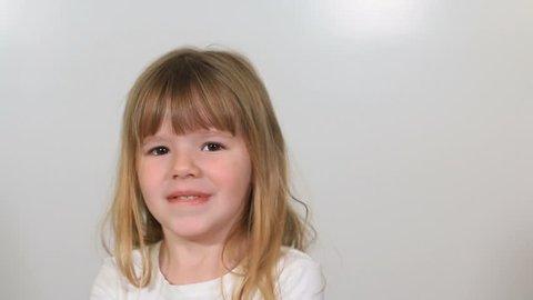 Cute little girl nodding in agreement against white background