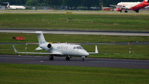 DUSSELDORF, GERMANY - JULY 23, 2017: Side view of Learjet 40 CS-TFO of OMNI Aviation taxiing to runway before takeoff