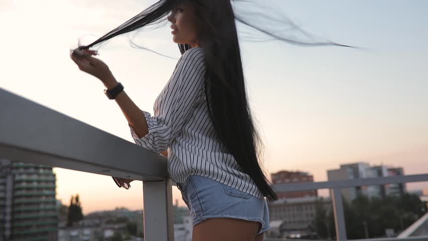 Well-groomed woman touching her beautiful hair on rooftop in sunset time
