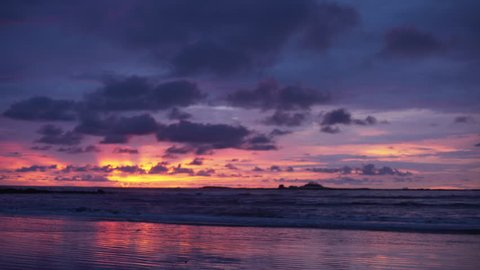 Out of focus background plate of beautiful orange, purple and blue sunset on the beach in Costa Rica for compositing or keying. Blurred defocused shot of ocean sun set for green screen composite. 4k