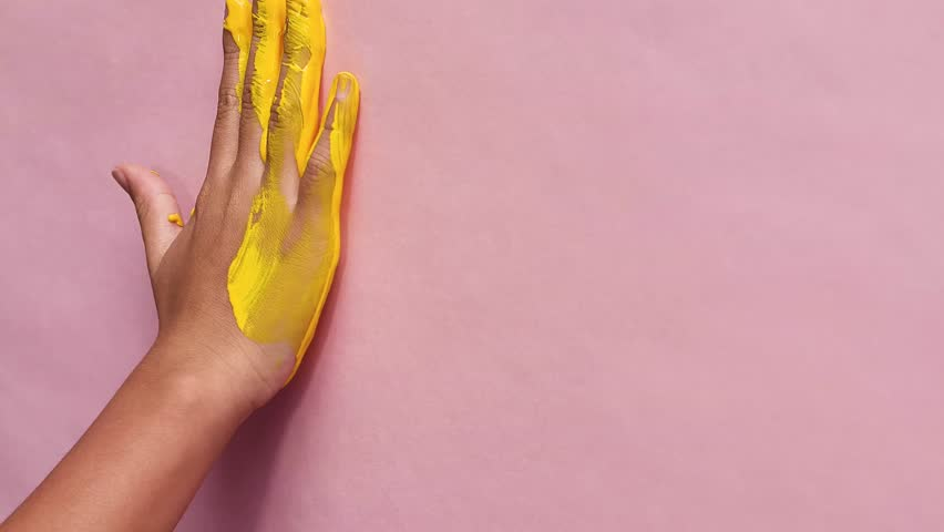 Girl painting yellow a handprint on paper.