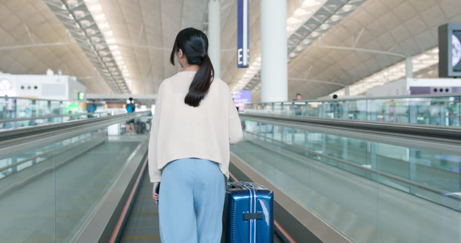 Woman walking into the airport with luggage | Shutterstock HD Video #1015029955