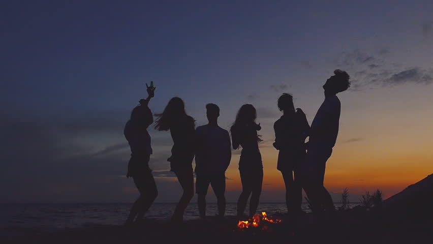 Group of people dancing at the beach near the bonfire. Slow motion. | Shutterstock HD Video #1015035655