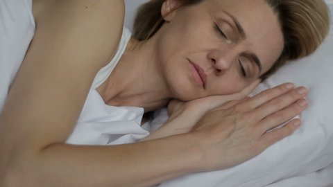 Middle-aged woman sleeping deeply, tranquilly, having delightful, positive dream