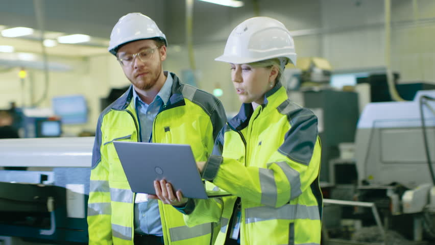 Male and Female Mechanical Engineers Talking, while Walking Through Industrial Factory, Male Holds Laptop. Modern Facility with Automatic Machinery Working in Background.