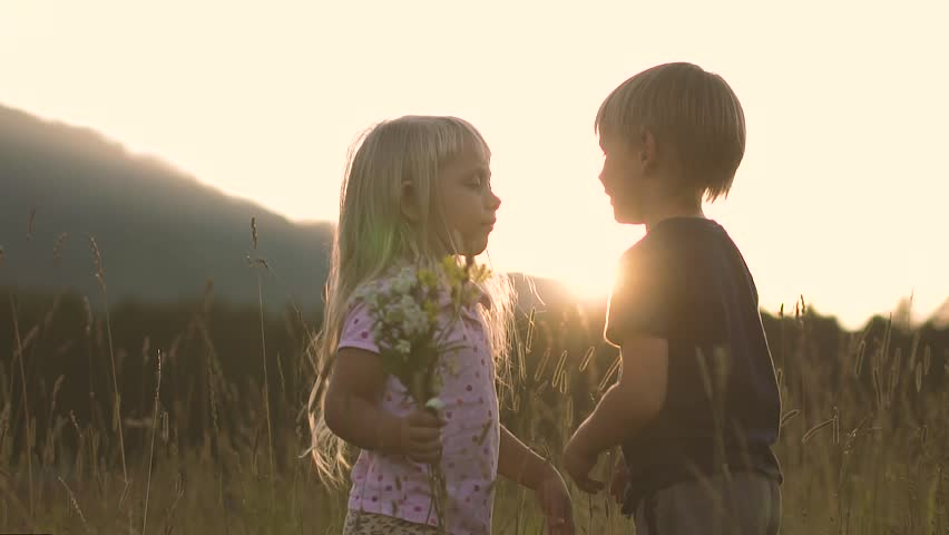 Little girl in the field at sunset, kisses the boy for what he gave her flowers | Shutterstock HD Video #1015052575