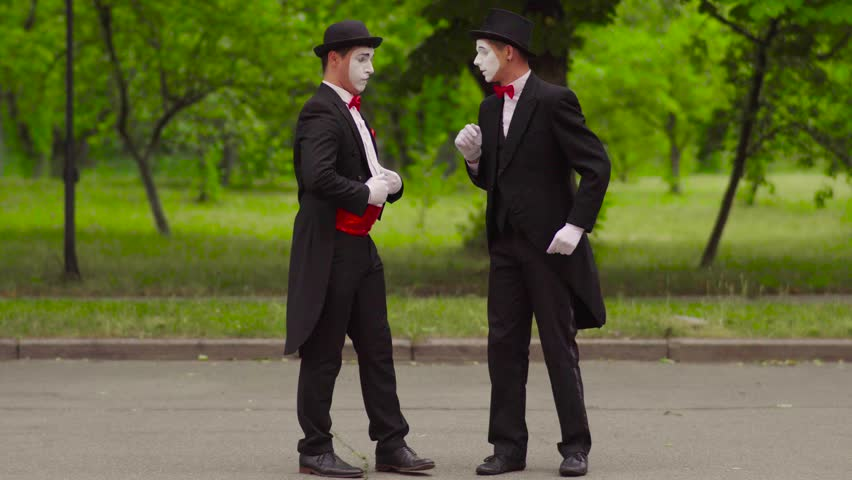 Two comical mimes do performance in the park