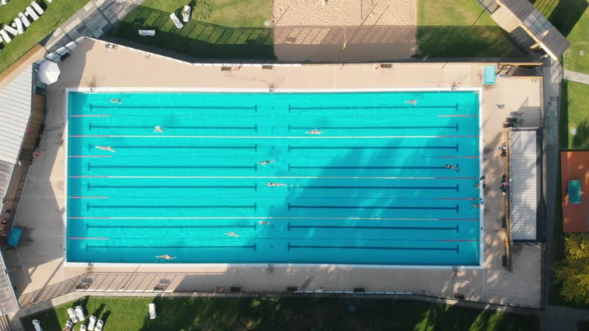 Swimmers practice in olympic pool aerial top down view. Luxury Resort swimming pool with clean beautiful blue water