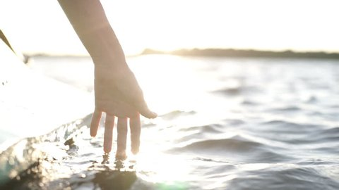 At sunset, close-up the hand of a girl moving through the water