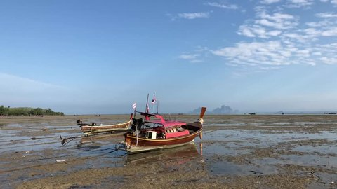 Long-tail fishing boats at the beach during low tide in Koh Mook, Thailand