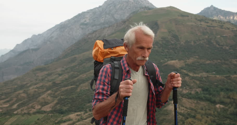 Old caucasian mountaineer hiking in mountains with backpack - tourism concept, closeup 4k #1015128595