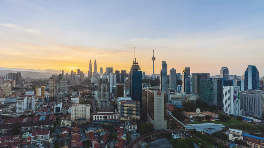 Time lapse: Beautiful and dramatic sunrise view of the Kuala Lumpur skyline and the national landmarks, the Petronas Twin Tower and KL Tower from night to day at dawn. High Quality 4K. | Shutterstock HD Video #1015141045