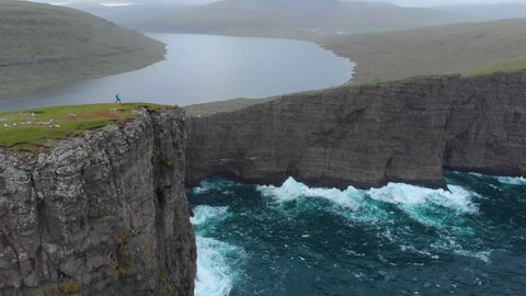 AERIAL: Young female traveller hikes up to edge of a cliff to see the breathtaking green landscape in moody Faroe Islands. Woman hiking in Scandinavia observes still lake and waves crashing into rocks