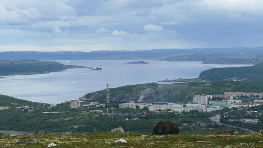The tundra landscape - a moss-covered hillside with large stones on the background of a large river with ships and buildings in the distance. Low mountains under a cloudy sky.