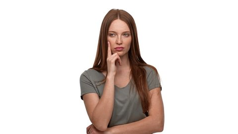 Portrait of ginger woman 20s touching chin and thinking about important things or doubting, isolated over white background. Concept of emotions