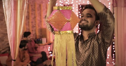 A smiling handsome man hanging a Diwali traditional lantern in a decorated house. A young male wearing kurta hanging colorful Diwali Kandil while his colleagues sitting and talking in the background