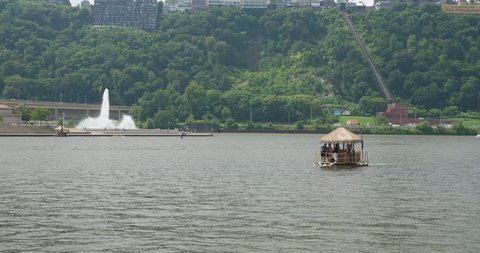 A small riverboat in the shape of a tiki bar carries tourists on the Allegheny River in Pittsburgh on a summer day. The fountain in Point State Park in the distance.