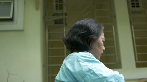 Senior woman in wheelchair having heart attack, Chest pain