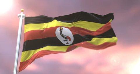 Flag of Uganda waving at wind in slow at sunset, loop