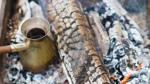 Coffee in Turkish is cooked in Cezve in hot coals and boils Men's hand removes coffee from coals.