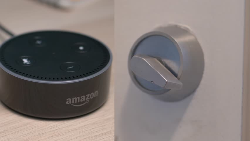MONTREAL, CANADA - August 2018 : Amazon Echo Alexa Dot opening a door lock of a home. Smart home device.