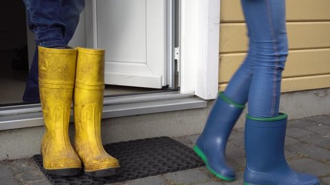Two people get into blue and yellow rubber boots in front of the house