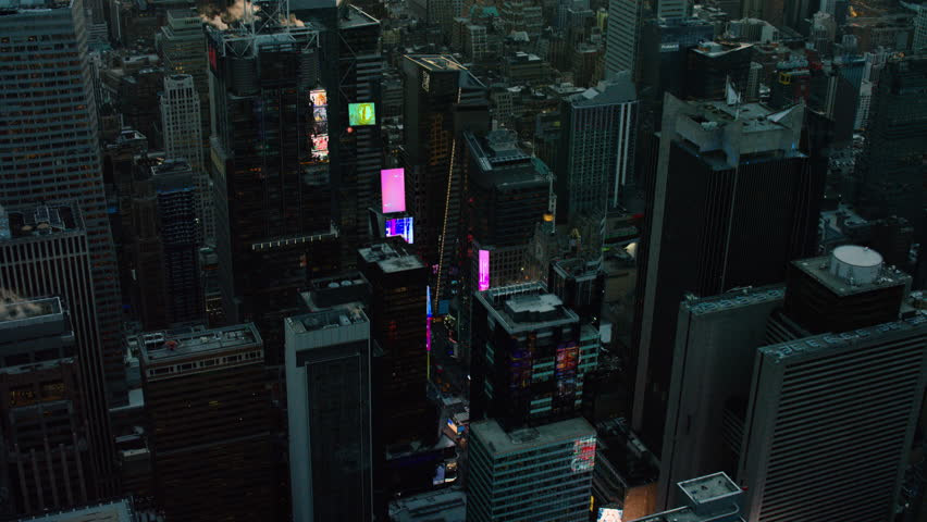 Aerial view of a large urban city at sunset. View of skyscrapers and Times Square advertisements in New York. Shot with a RED camera. 4k footage.