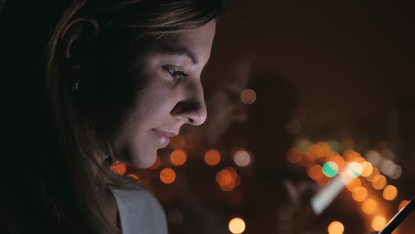 Side view close up portrait of a beauty woman standing by the window in the evening in the dark, outside window romantic illumination of the night city, uses a smartphone, screen illuminates the face #1015310755