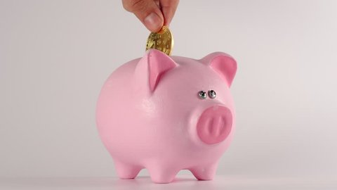 Male hand throws bitcoin into a pink piggy moneybox