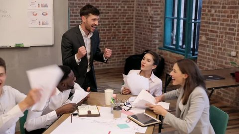 Creative Business Team Having Meeting at the Office. Successful Deal. Business Partners Concluding a Contract. Positive Emotions. Interethnic Group of Business People. People Starting to Throw Papers.