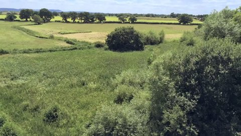 Aerial view, up move. Drone rise panorama of plain and fields in Cheshire.