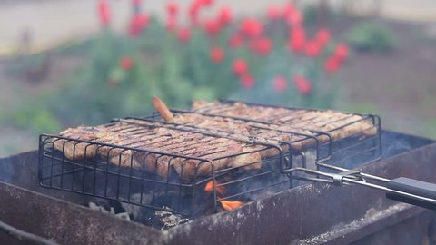 Grilled pork steaks on the grill in the garden, springtime, close up.