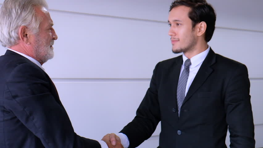 Two businessmen shaking their hands, young businessman and senior businessman big deal contract or success business after sign contract.